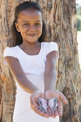 Little girl holding a butterfly in the park smiling at camera on a sunny day