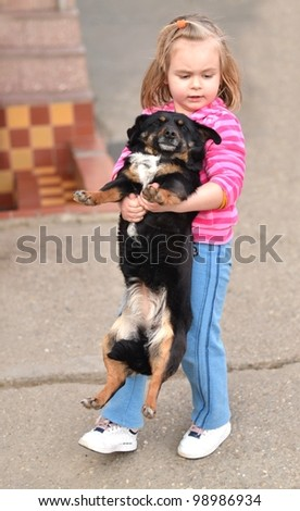 Little girl holding a dog in her arms