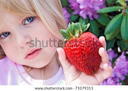 little girl holding a large strawberry