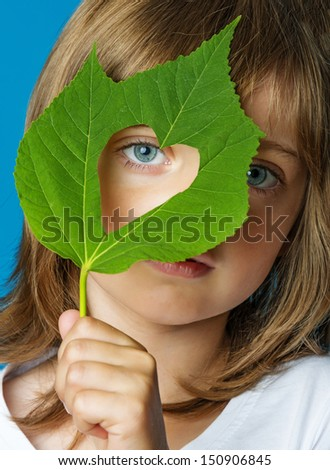 little girl holding a leaf with heart shape - ecology concept