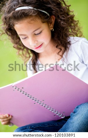 Little girl holding a notebook and studying at the park