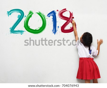 little girl holding a paint brush painting happy new year 2018 on a white wall background #704076943