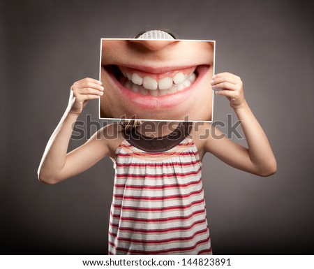 little girl holding a picture of a mouth smiling