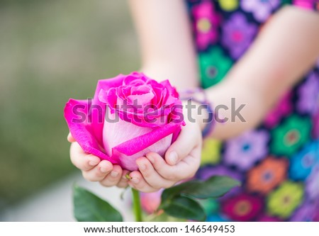Little girl holding a pink rose. Mothers day concept