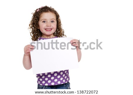 Little girl holding a plain white sign isolated on a white background smiling at the camera