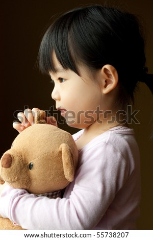 Little girl holding a teddy bear in her hand