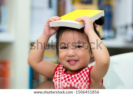 Little Girl holding Books on Head. Cute Young Toddler Sitting On A Chair Near Table and Reading Book. Child reads in a bookstore, surrounded by colorful books. Library, Shop, Shelving In Home.