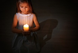 Little girl holding burning candle in darkness