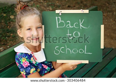 Little girl holding chalkboard with words back to school. Outdoor photo