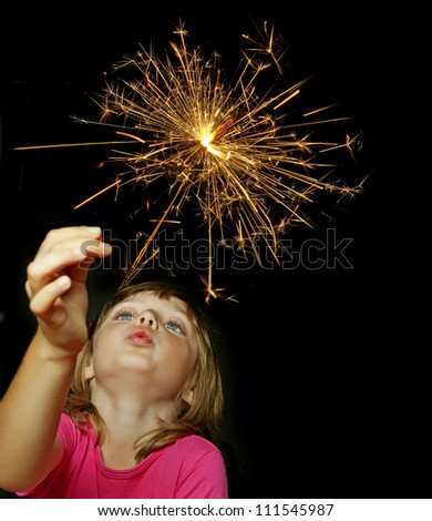 little girl holding firewors on black background #111545987