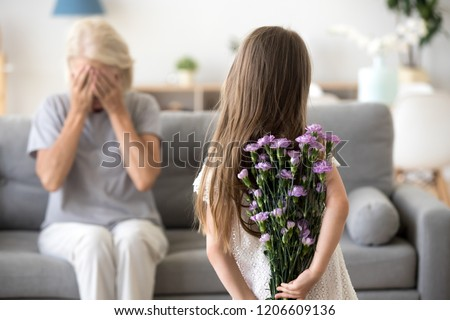 Little girl holding flowers making surprise for grandmother, congratulating her with birthday, excited granny sit with eyes closed, small grandchild prepare gift standing with bouquet in hands