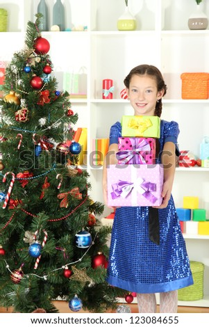 Little girl holding gift box near christmas tree