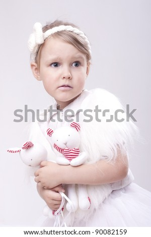 Little girl holding handmade toys in white background