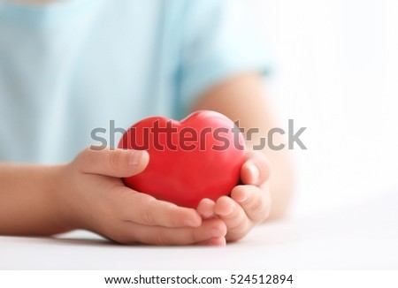 Little girl holding heart in her hands