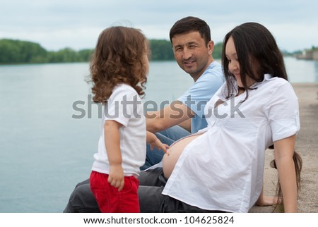Little girl holding her mothers pregnant stomach while outdoors