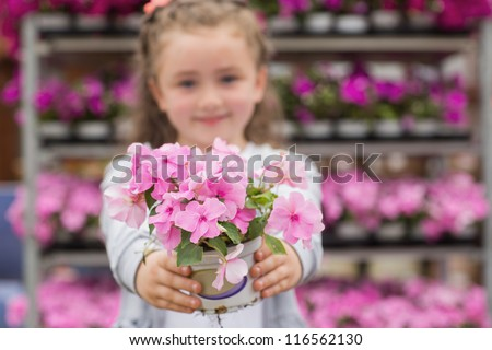 Little girl holding pink flowers out in garden center