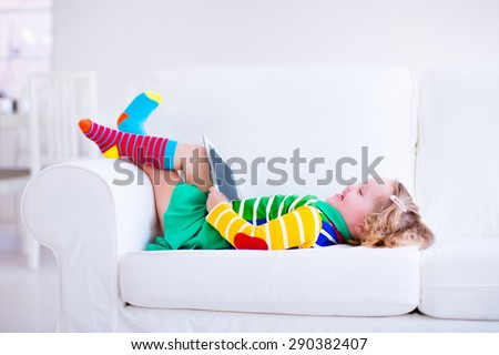 Little girl holding tablet pc relaxing on a white couch. Kids using computer at home or preschool. Children learning with digital devices. Child playing online game. Toddler kid and modern gadget.