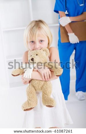 little girl holding teddy bear in doctor\'s office