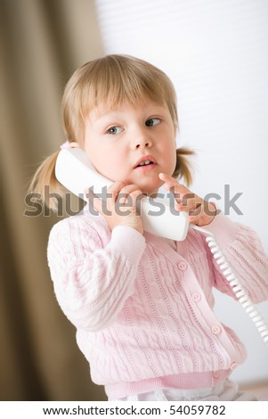 Little girl holding telephone receiver calling at home