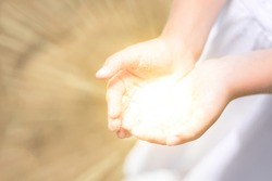 Little girl holding the sun in her hands. bright light comes from the hands of child. concept miracle, magic, share, give, offer, care