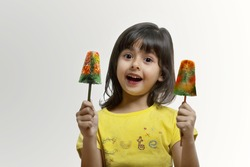Little girl holding two ice lollies