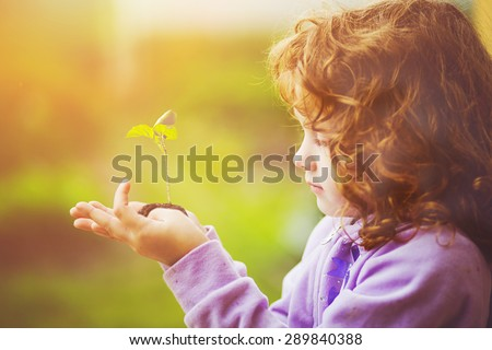 Little girl holding young plant in spring outdoors. Ecology concept. Background toning to instagram filter. #289840388
