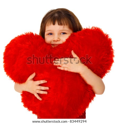 Little girl hugging a large toy heart isolated on white background