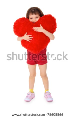 Little girl hugging a toy heart, isolated on a white background