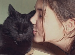 Little girl hugging and kissing a black kitten Maine Coon