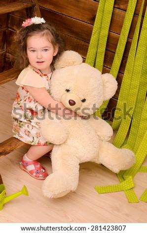 little girl hugging big teddy bear indoors