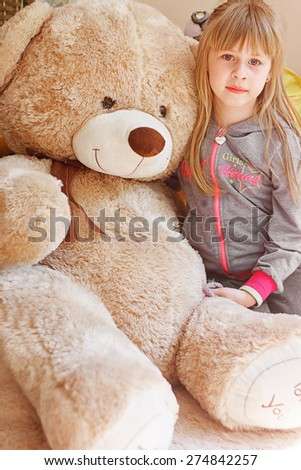 little girl hugging big teddy bear while sitting on chair