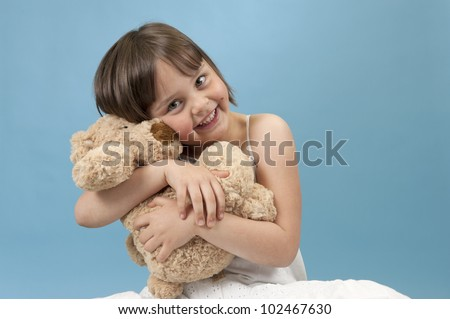 little girl hugging her teddy bear