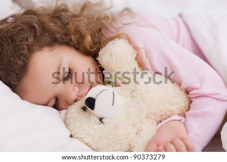 Little girl hugging her teddy while sleeping