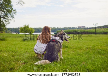 Little girl hugging Husky dog while sitting in fleid and enjoying beautiful view. Friendship between pet and owner