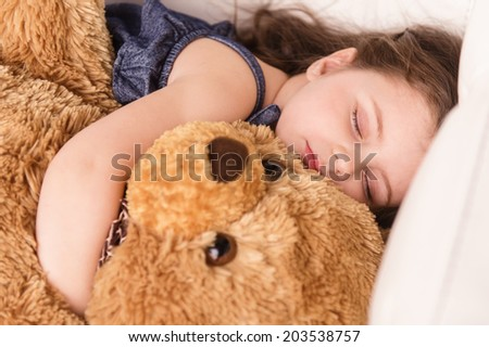 little girl hugging teddy bear. closeup view of nice girl sleeping