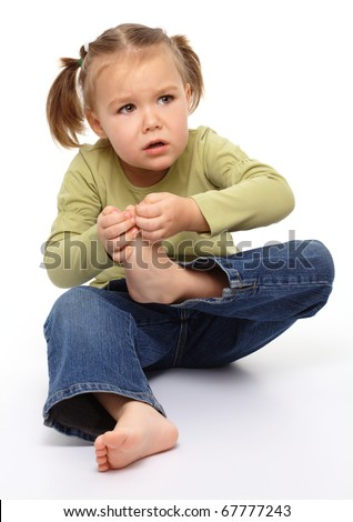 Little girl hurt her tiptoe, feeling pain, isolated over white