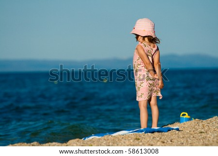 Little girl in a beautiful dress standing on the beach and looks into the distance.