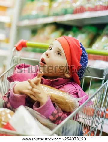 Little girl in a big store with products in the cart.