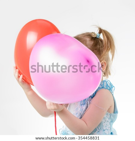 Little girl in a blue dress holding a red balloon in the shape of a heart on a white background #354458831