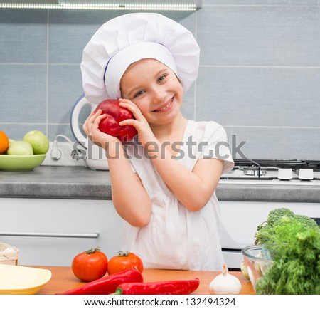 little girl in a cap chef in the kitchen with Pepper