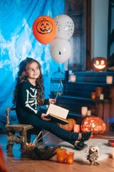 Little girl in a costume of skeleton holding balloons; Halloween studio decoration