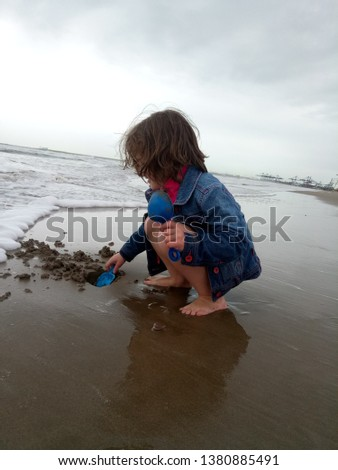 little girl in a denim jacket playing with wet sand near the sea, in cold weather, on the beach against the background of the port of Valencia. Picture taken April 23, 2019, Malvarrosa beach, Valencia