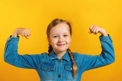 Little girl in a denim shirt with pigtails made of hair on a yellow background. The child shows strong hands. Education concept, school, success, power, feminism.