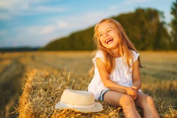 Little girl in a field with hay rolls at sunset