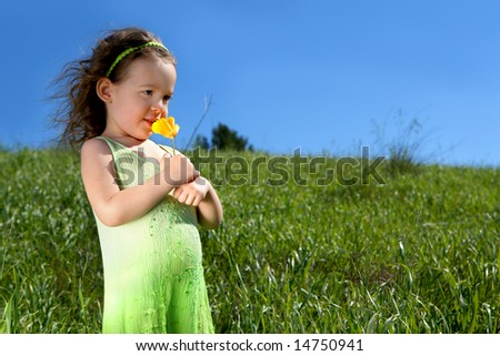 Little girl in a grassy meadow smelling an orange poppy