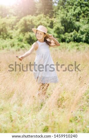 Little girl in a hat runs on a golden meadow #1459910240