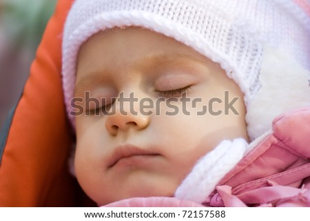 little girl in a pink jacket sleeps in a carriage