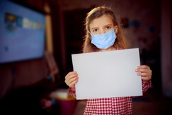 Little girl in a protective mask, pajamas holds a blank sheet of paper while standing in room at home, Protection against coronavirus.