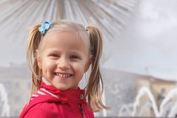 Little girl in a red jacket with two ponytails on his head on a blurred fountain background