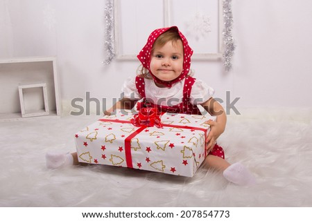 little girl in a red kerchief holding a big gift with red ribbon, holiday, new year, white background